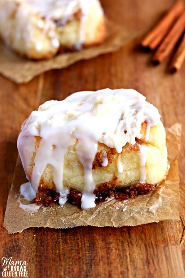 gluten-free-cinnamon roll with another cinnamon roll and cinnamon sticks in the background