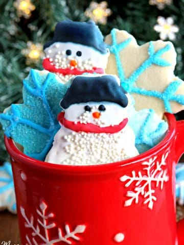gluten-free sugar cookie cut outs in snow man and snowflakes in a red cup with a Christmas tree in the background