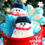 gluten-free cut out sugar cookies snowmen and snowflakes in a red snowflake cup