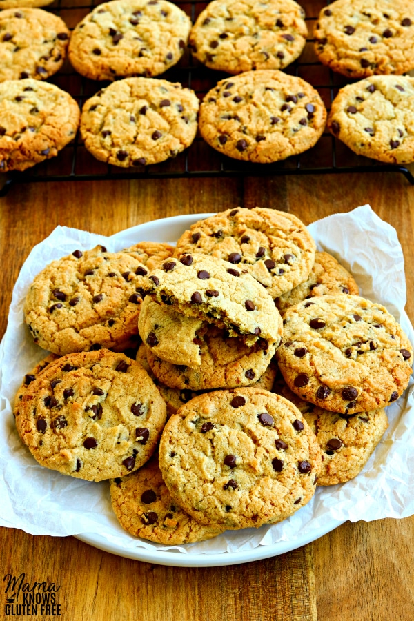 a plate of gluten-free and dairy-free chocolate chip cookies with more cookies on a cooling rack in the background