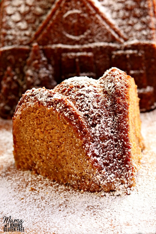 slice of gluten-free gingerbread cake with a gingerbread cake house in the background