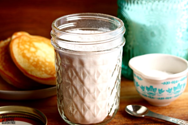 mason jar of gluten-free pancake mix with a measuring spoon, measuring cup, sugar jar and a plate of pancakes in the background