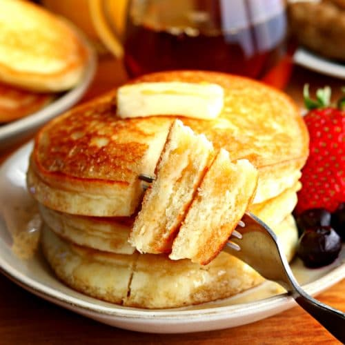 a stack of 3 gluten-free pancakes cut with a bite on a fork with butter, syrup, blueberries and strawberry on a plate with syrup, sausage, orange juice and a plate of pancakes in the background