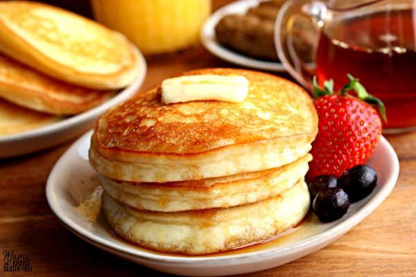 stack of three pancakes with a strawberry and blueberries on a plate with sausage, syrup, orange juice and a plate of pancakes in the background