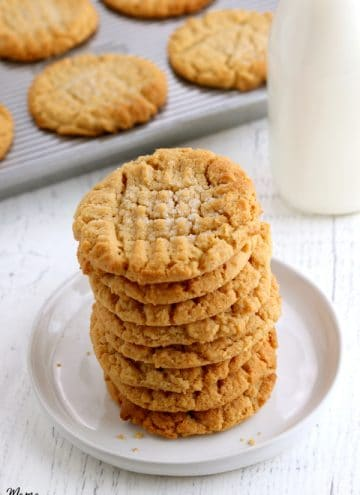 stack of gluten-free peanutbutter cookies with tray of cookies and milk in the background