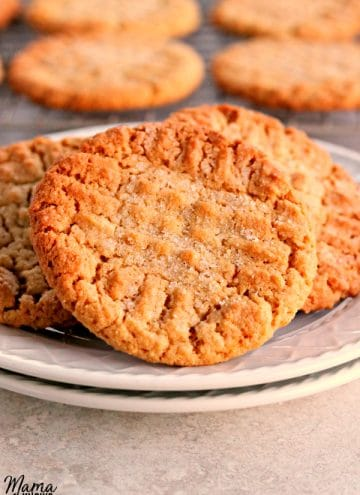 gluten-free peanut butter cookies on a plate with cookies on a cooling rack in the background