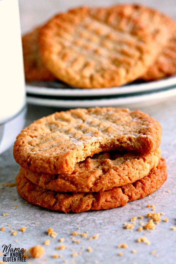 3 gluten-free peanut butter cookies stacked with a bite out of one and a plate of cookies and a glass of milk in the background