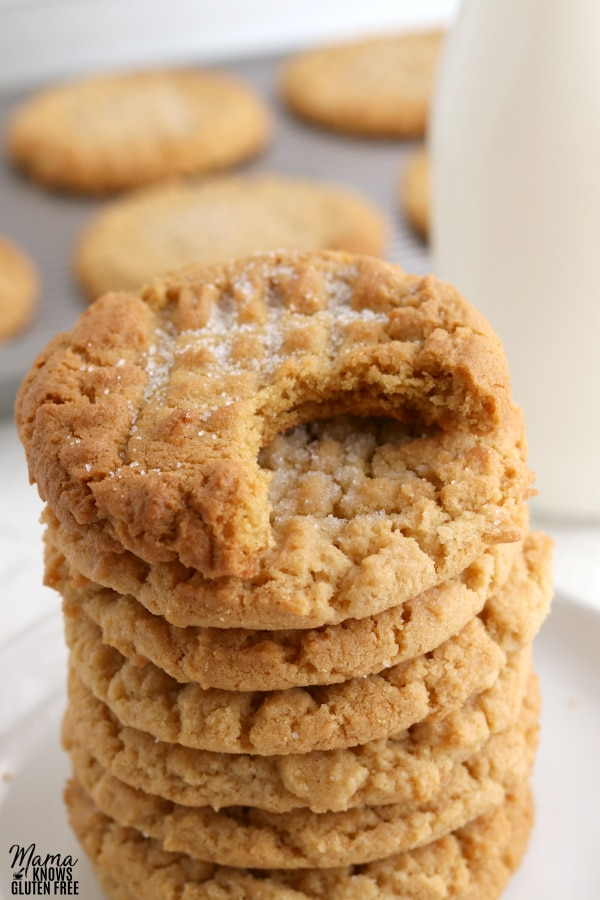 stack of gluten-free peanut butter cookies with the top cookie with bite out of it