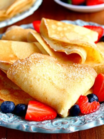 a plate full of folded gluten-free crepes with strawberries and blueberries with crepes and strawberries in the background