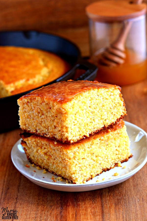 2 pieces of gluten-free cornbread stacked on top of each other with a skittlet of cornbread and honey jar in the background