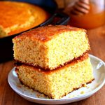 2 slices of gluten-free cornbread stacked on top of each other with a honey jar and a skillet of cornbread in the background