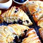 cooing rack with gluten-free blueberry scones with blueberries and a cup of coffee on the background