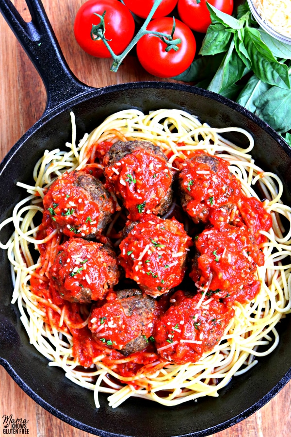 gluten-free meatballs on top of spaghetti covered in tomato sauce with basil and tomatoes in the background
