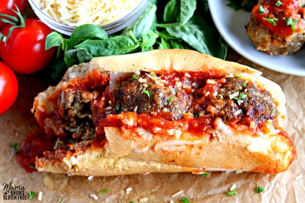 gluten-free meatball sub with Parmesan cheese, basil and meatballs in the background