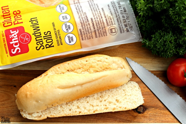 Scahr sandwich roll cut in half with knife, parsely and packaging in the background