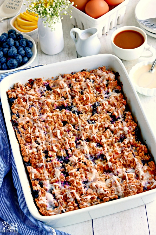 a pan of gluten-free blueberry breakfast casserole with blueberries, lemon, egg, flowers, coffee, cream and glaze in the background.