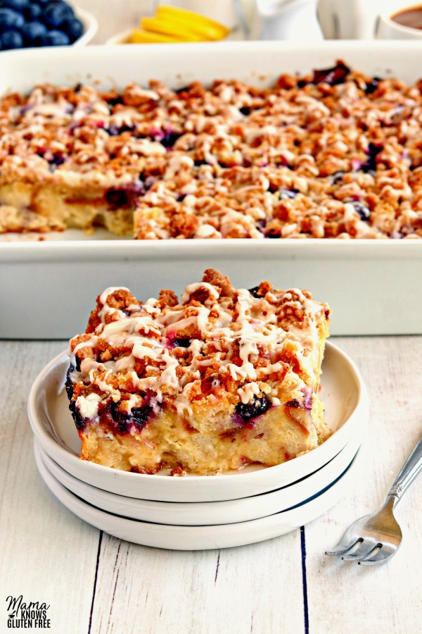 a slice of gluten-free blueberry breakfast casserole on a plate with the casserole in the background