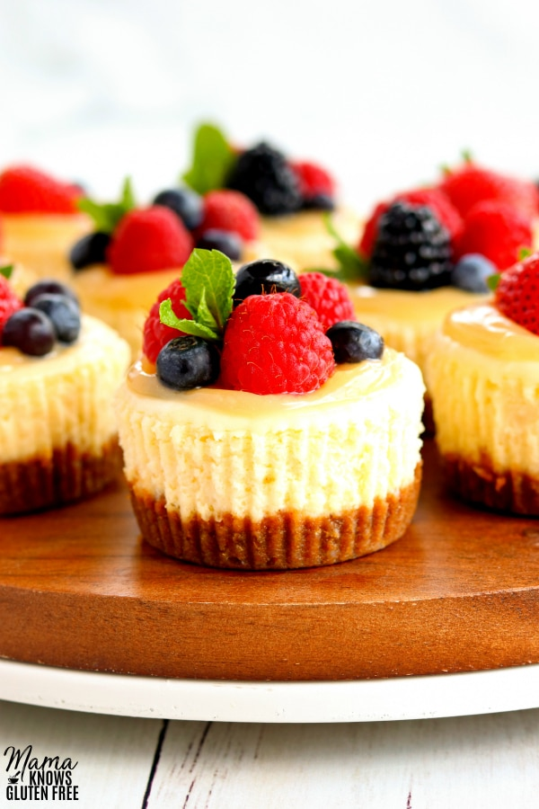 zoomed in shot of gluten-free min cheesecakes topped with lemon curd and berries