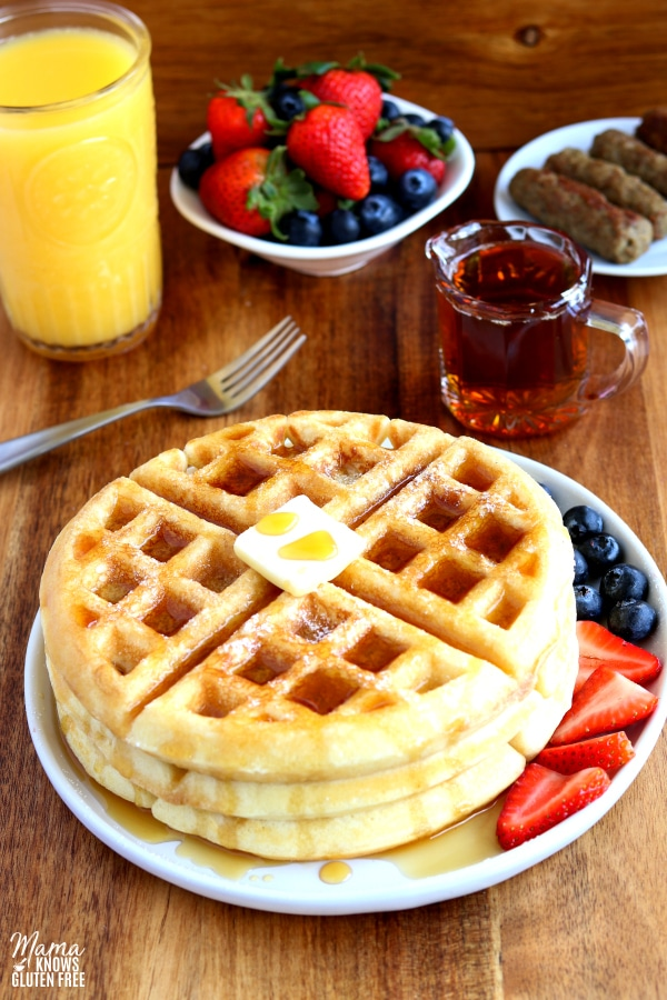 3 gluten-free waffles on a plate with berries with syrup, sausage, berries and a glass of orange juice
