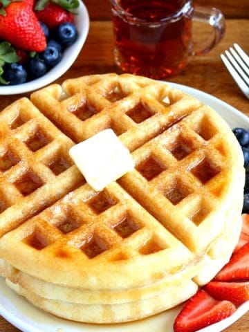 gluten-free waffles with butter and syrup on a white plate with berries. A fork, syrup and berries in the background.