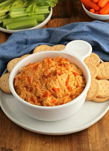 bowl of buffalo chicken dip with crackers and celery and carrots in the background