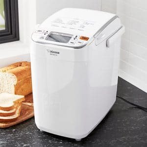 Zojirush bread machine with loaf of bread in the background