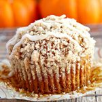 gluten-free pumpkin muffin with crumb topping and pumpkins behind it
