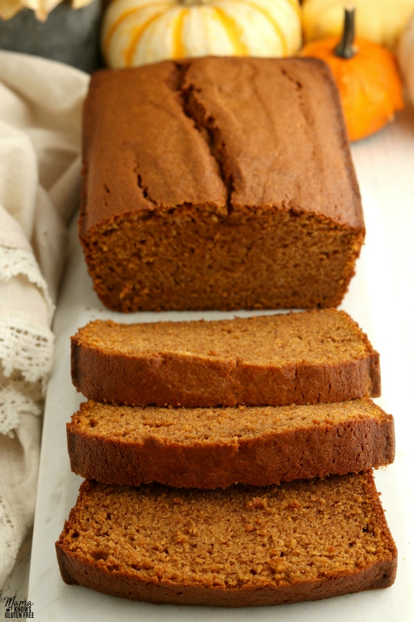loaf of gluten-free pumpkin bread with 3 slices cut out of it