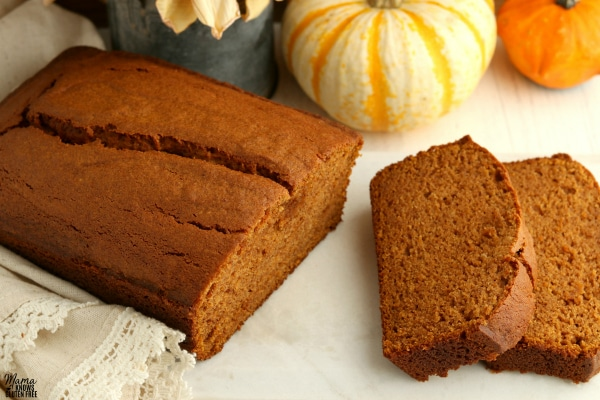 gluten-free pumpkin bread with two slices and pumpkins in the background