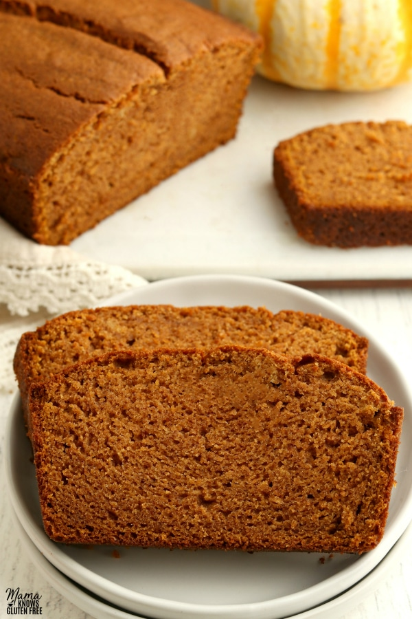 2 slices of gluten-free pumpkin bread on a white plate with the loaf and another slice in the background