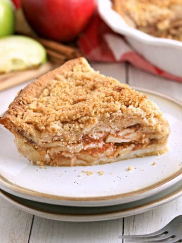 slice of gluten-free apple pie on a white plate with a fork with pie and apples in the background