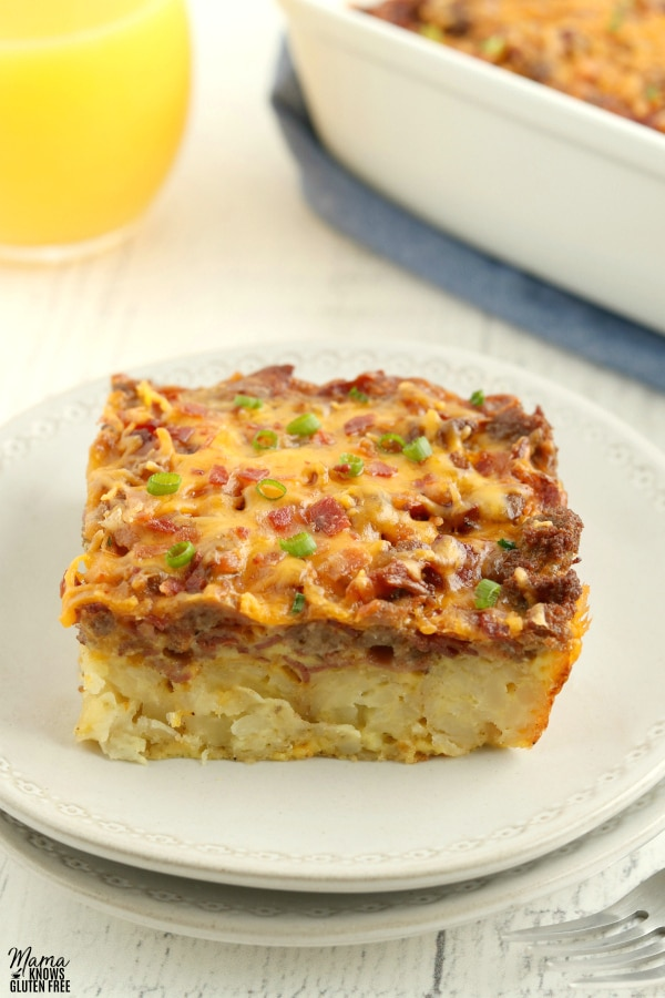piece of gluten-free breakfast casserole on a plate with a glass of OJ and the casserole in the background
