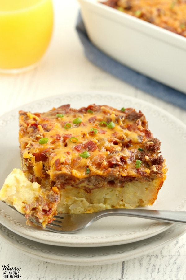 piece of gluten-free breakfast casserole on a plate with a fork with the casserole and glass of orange juice in the background