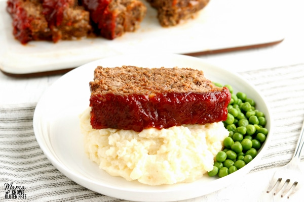 a plate with a slice of gluten-free meatloaf with green peas and mashed potatoes with the meatloaf in the background