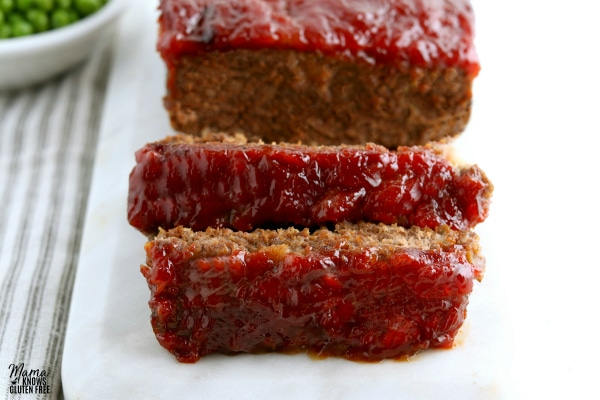 a gluten-free meatloaf with two slices cut into it on a white platter