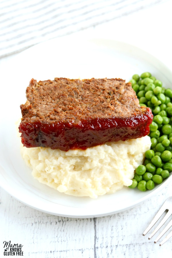 a slice of gluten-free meatloaf with mashed potatoes and green peas