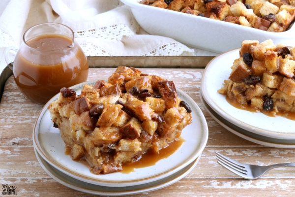 two servings of gluten-free bread pudding on white plates on a wooden tray with caramel sauce and baking dish in the background