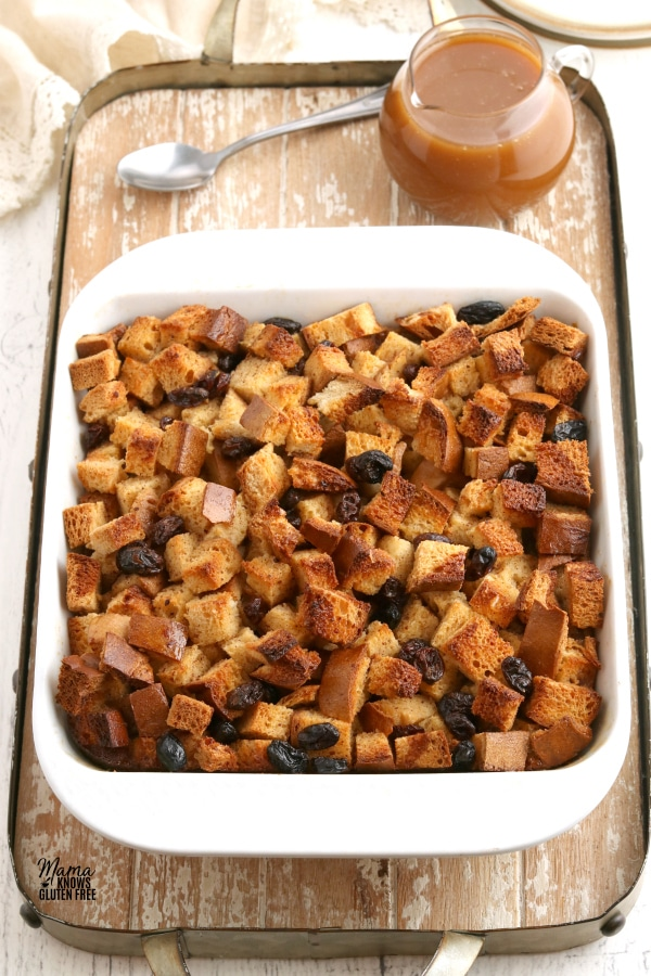 baking dish of gluten-free bread pudding with caramel sauce on a wooden tray