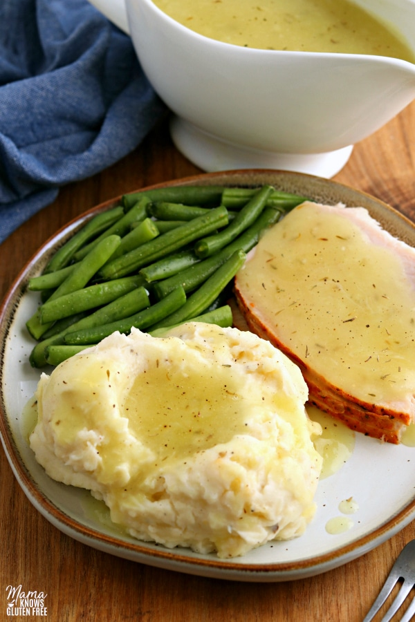 plate of mashed potatoes with gluten-free gravy, turkey with gravy and green beans