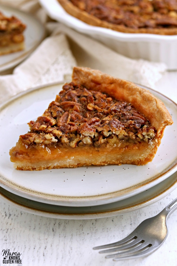 slice of gluten-free pecan pie on a white plate with a fork and the pie in the background