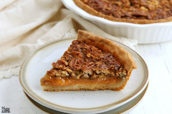a slice of gluten-free pecan pie on a white plate with the pie in the background