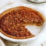 gluten-free pecan pie with a slice cut out of it with plates in the backgorund