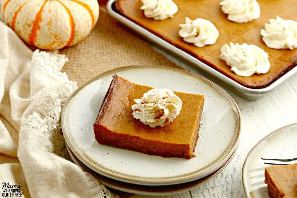 two gluten-free pumpkin pie bars on plates with the bars and pumpkins in the backgorund