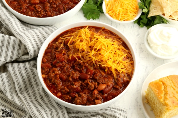 bowl of gluten-free chili with cornbread and chili toppings in the background