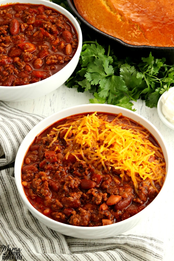 2 bowls of gluten-free chili with cornbread and clintro in the background