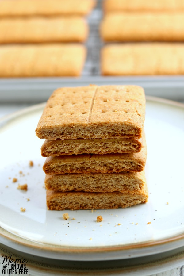 gluten-free graham crackers stacked on top of a white plate with more graham crackers on a cookie sheet in the background