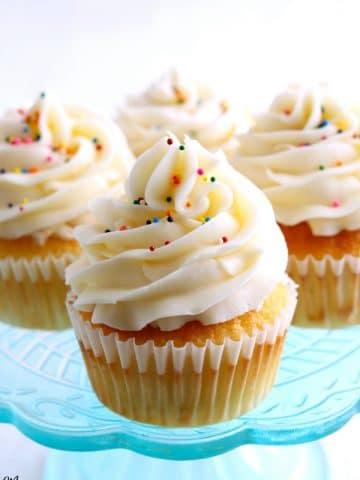 4 gluten-free vanilla cupcakes on a blue cake plate