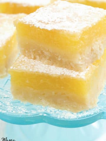two gluten-free lemon bars stacked on top of each other with more bars in the backround