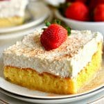 slice of gluten-free Tres Leches Cake with the cake and strawberries in the background