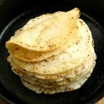 gluten-free tortillas stacked in a cast iron pan